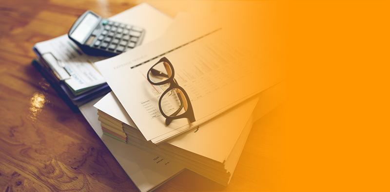 Okulary ikalkulator leżące nastercie dokumentów